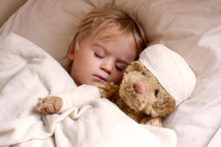 Kind schläft mit Bär im Arm