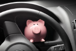 Sparschwein im Auto auf dem Lenkrad