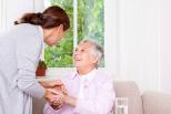 ältere Frau wird von Krankenpflegerin betreut