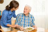 älterer Mann wird von Frau versorgt